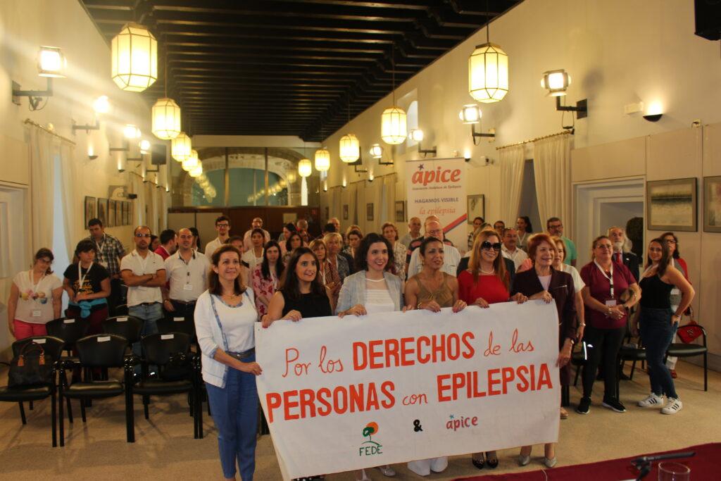 Los diputados presentes junto con la presidenta del parlamento y la de Ápice sostienen la pancarta. Por los derechos de las personas que tienen Epilepsia.