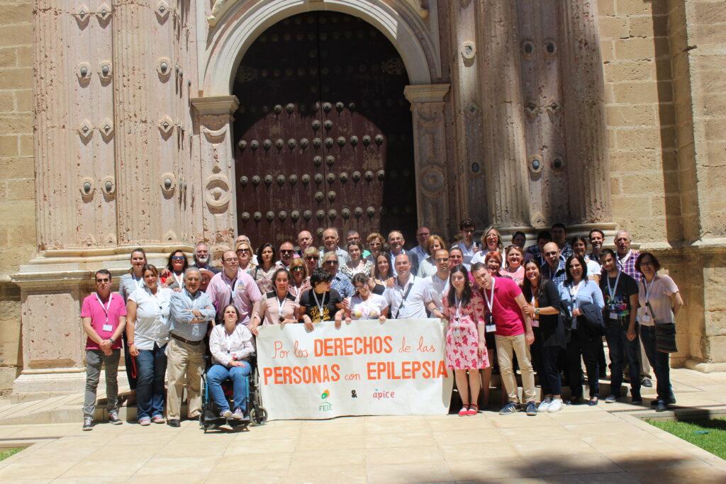 Las familias de Ápice en la puerta del parlamento de Andalucía sostienen la pancarta. Por los derechos de las personas que tienen Epilepsia